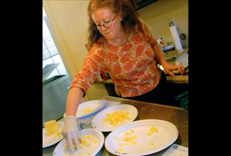 Flathead Lake Cheese maker Wendy Arnold arranges samples of the company's cheeses during the open house on Small Business Saturday.