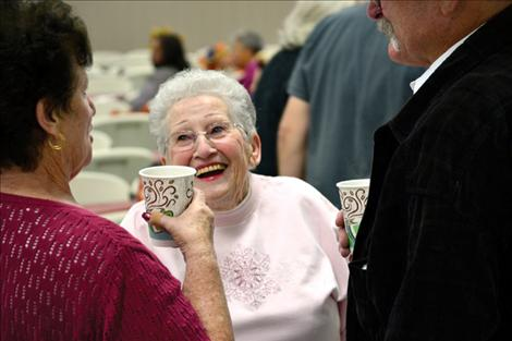 Marie Cowen shares a laugh with friends who gathered Thursday at the Ronan Community Center. Cowen started the free holiday dinner in 1997.