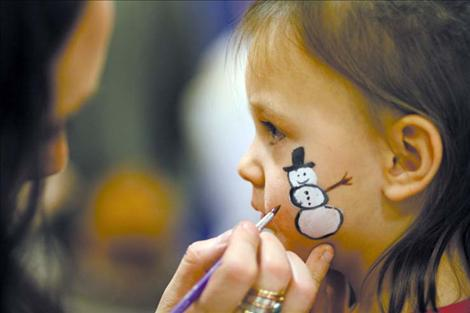 RaLynn Brown paints a snowman on Kaycee Best's cheek during the annual St. Ignatius Chamber of Commerce Christmas Carnival.