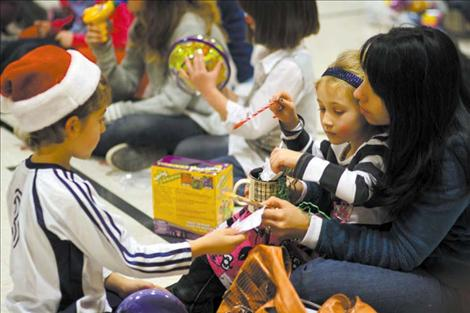 Two cheerful St. Ignatius children played with their newly-won door prizes as the festivities began to wind down Saturday night.