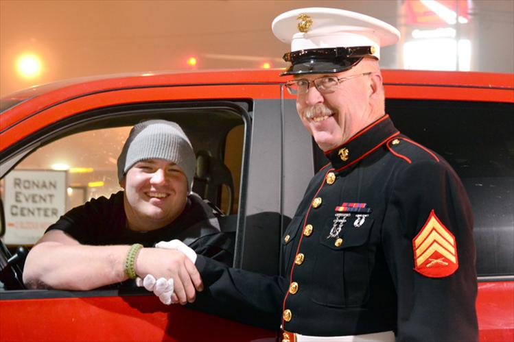 Marine Sgt. Chuck Lewis greets Tomy Parker.