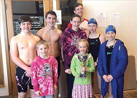 Lake Monsters Gabe Mergenthaler, Landon Shipley, Elissa Crist, Tiana Crist, Hannah Simpson, Amelia Stene and Teague McElwee and Missoula YMCA swimmer Jacob Butler hold the 2016 Montana Swimming Food Drive trophy.