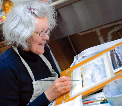 Watercolorist Jean Stromnes paints  a landscape and answers questions during the Dec. 7 art walk in downtown Polson.