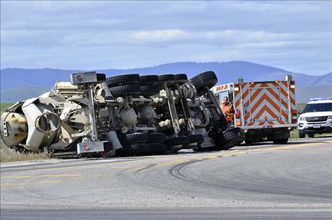 A full cement truck sits on its side after turning westbound onto Highway 212 Friday afternoon.