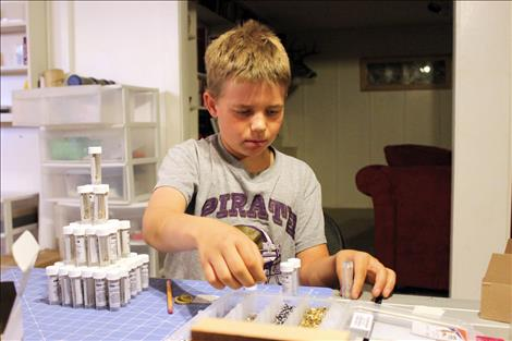 Brock Sturm, center, helps assemble a GearPod survival kit in his family basement.