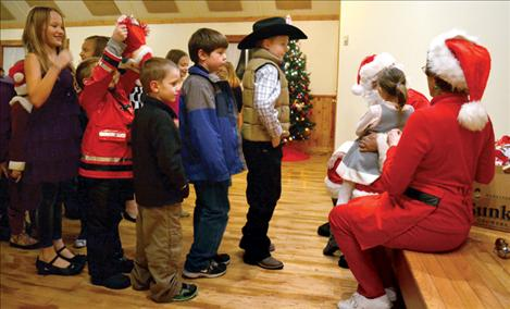 Children try to be patient as they wait to talk to Santa at the North Crow Clubhouse.