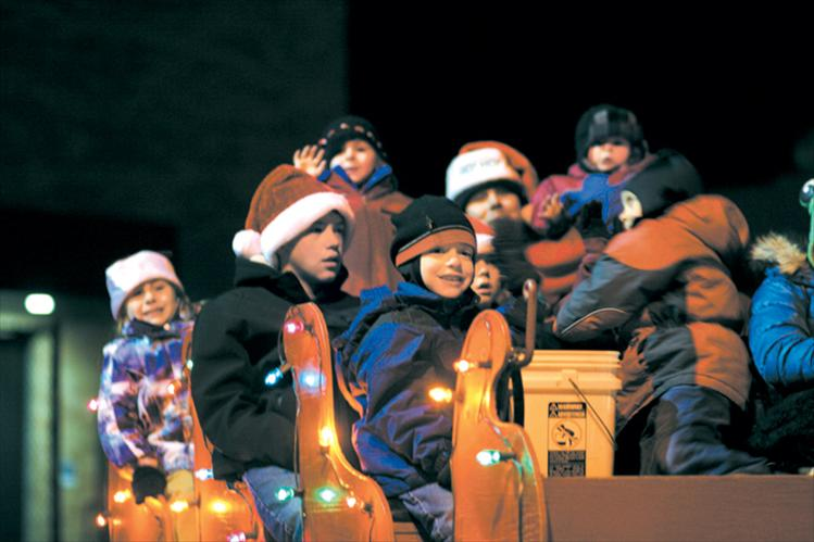 Children and grandchildren of the Bartel, McClure and Shima families smile and wave in the Starlite Motel's Santa sleigh float.