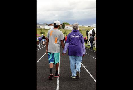 Darian Williams walks the survivor lap with his grandmother, Nancy Williams, druing the 2016 Lake County Relay for Life event July 8 in Polson.