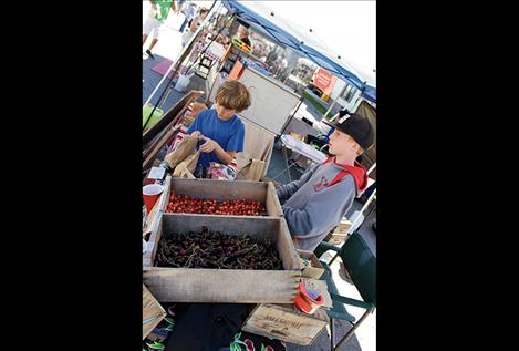 Jeremy Cromwell, left, sells cherries from their family orchard with the help of friend Carter Rawson.