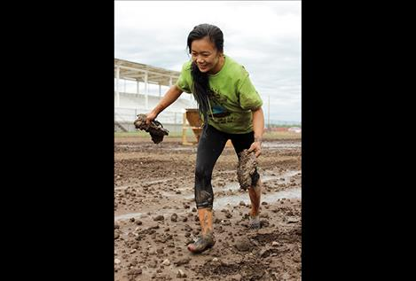 Marygold Houk removes her mud-caked shoes to finish, and below right, scrambles over a fence obstacle.