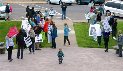 Demonstrators held signs outside the courthouse while couple charged with aggravated animal cruelty appear in Lake County courthouse.