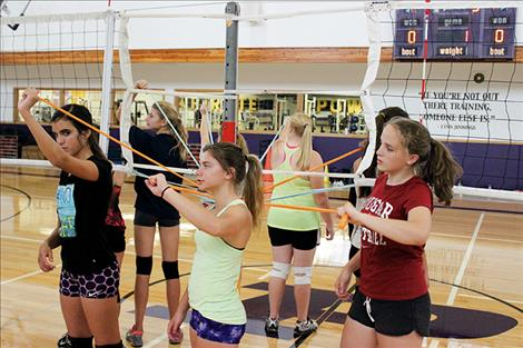 Lady Pirate volleyball team members do arm strengthening exercises.