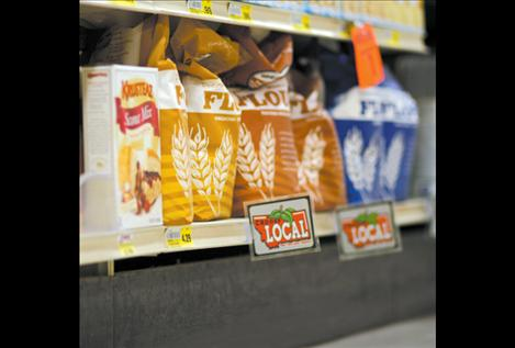 """Signs that read, """"Choose Local: Fresh from your neighbor"""" identify locally produced goods on Harvest Foods' shelves."""