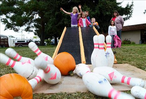 Sisters Kyra and Kestin Marmon and their cousin Ysabel Smith bowl with pumpkins at Saturday's Harvest Fest in Ronan. Above