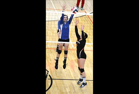 Mission's Afton Brander goes up for a block against Ronan's Shaina Snyder during a Sept. 22 game in Ronan.
