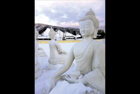 Snow covers ground, mountains and statues alike during a chilly sunset at the EWAM Garden of 1,000 Buddhas