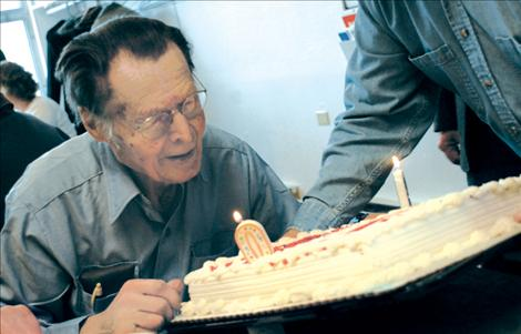 """Orville Bjorge blows out the candles on his birthday cake. His nephew Marvin said he didn't dare put 90 candles on the cake, so there was a """"9"""" and a """"0."""""""