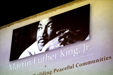A projected banner with Dr. Martin Luther King Jr.'s picture hangs above the crowd and panelists as the discussion began.
