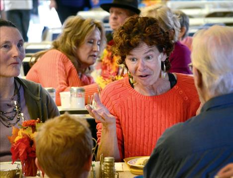 Kim Schmidt visits with new friends at Polson's Community Thanksgiving dinner.