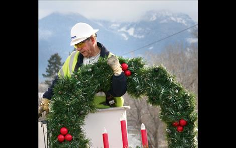 The last of more than 300 wreaths hung during Jim Boyer's career with Mission Valley Power is mounted Nov. 29 in Polson.