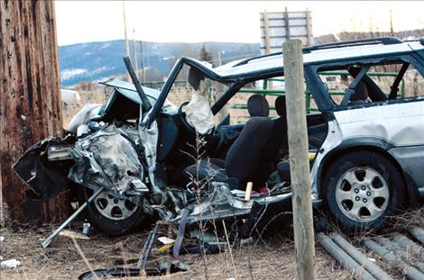 A power pole stopped the Subaru station wagon after the car hit a fence.