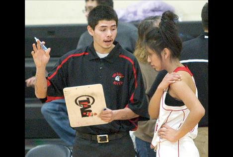 Lady Eagles assistant coach Artie Mendoza talks strategy with Ruby Saluskin before Friday night's game.Mendoza played for the Two Eagle River boys' basketball team last year.