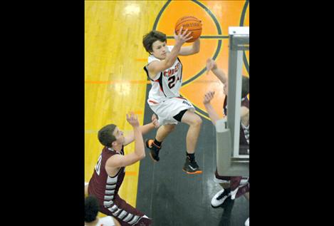 Sophomore Colton McCrea soars over two Hamilton players Friday night on his way to the bucket.