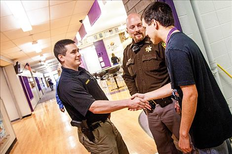 Brian Hines and Nate Lundeen greet student John Baker Street at Polson High School.