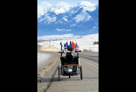 Lewis' stroller, containing all his equipment and displaying a flag from every branch of service, rolls unattended down Ravalli hill toward St. Ignatius.