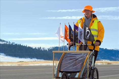 Decked out in bright reflective clothing, Ronan resident and Marine veteran Chuck Lewis trains along U.S. Highway 93 in preparation for his 3,300-mile walk across America.
