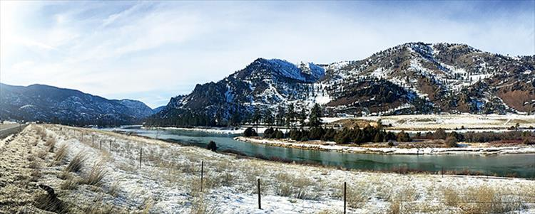 The Flathead river appears emerald green as it winds along Hwy. 200 on a sunny, winter day.