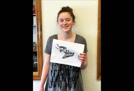 Charlo student Allie Delaney displays the design she created for the race-day shirts that will have a purple and white color scheme.