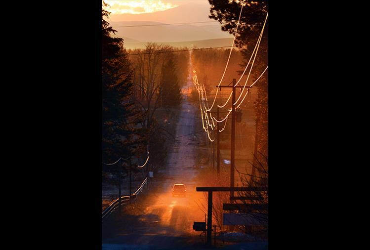 The setting sun illuminates electrical lines along Courville Trail east of Pablo Thursday evening.