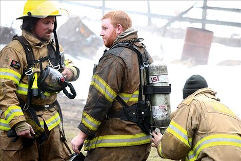 Ronan Volunteer Firefighters get their breathing apparatus replaced after exiting the smoky home,