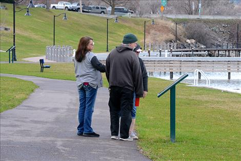 Folks stop to read one of the informative signs at Sacajawea Park Thursday afternoon.