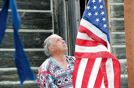 Fort Connah Restoration Society President Al Williams raises the flag during the opening ceremony.