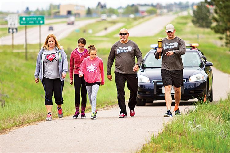 CSKT Police Chief Craige Couture, CSKT Fish and Game officer Brandon Couture and family carry the torch for Special Olympics Friday morning, along U.S. Highway 93 toward Pablo.