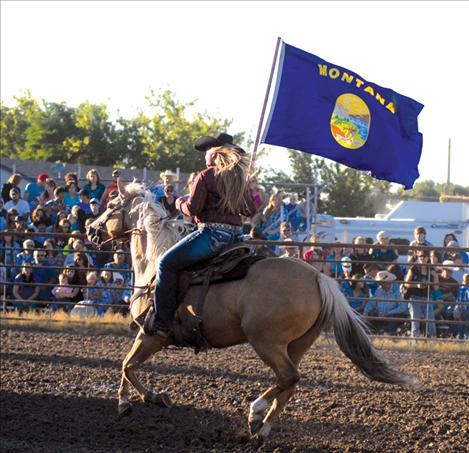 Michaela Blevins circles the arena bearing the Montana flag.