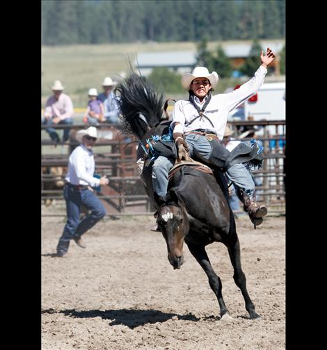 Browning cowboy Andrew Whiteman rides saddle bronc at the Ronan Pioneer Days Rodeo Sunday afternoon.