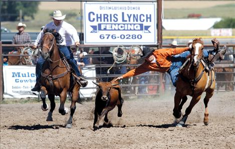 Weston Mallin leans from his horse to take down a steer.