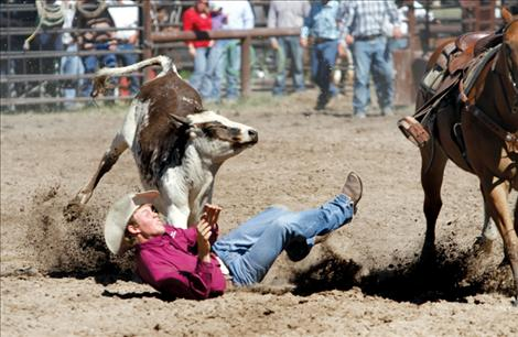 2012 Montana state high school steer wrestling champion Will Powell hits the dirt as his steer steers clear of the incoming cowboy.