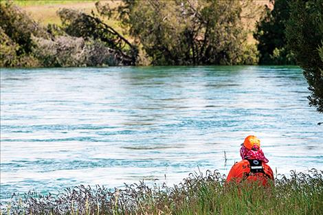 A Lake County Search and Rescue team member watches the Flathead River for the missing man.