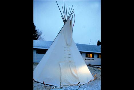 Light from the stove and lantern shines through the walls of the teepee. To raise awareness of homelessness, people are spending the night in the teepee to raise money for renovations on a homeless shelter.