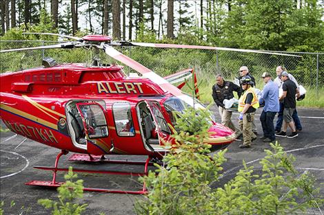 One of the six people transported by air ambulance following a deck collapse at Glacier Camp near Lakeside is carried to a helicopter