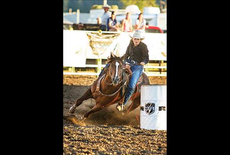 Polson cowgirl makes the turn on barrel two.