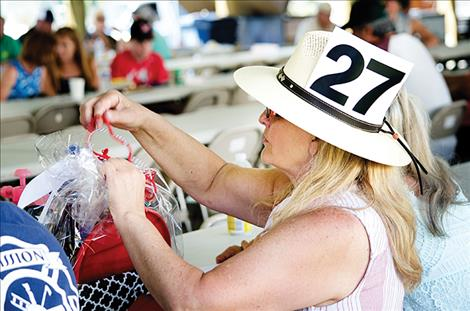 her bid number in her hat  as she looks at  an item she  bought from  the auction to  support the volunteer  fire department.