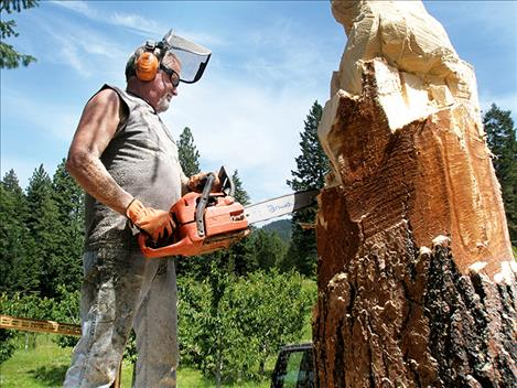 Todd Coats works on a mama grizzly bear and cubs woodcarving.