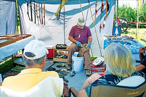 A small crowd gathers to watch  Don Safford as he works on chiseling down flint to make an arrowhead.