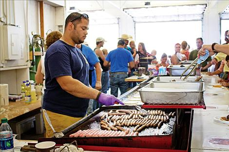 Volunteer fireman TJ Sheridan prepares sausages for visitors at the Arlee Fireman's Breakfast.