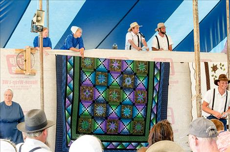 Karen Peterson/Valley Journal Auctioners sell off colorful quilts created by Amish communities all over the country.